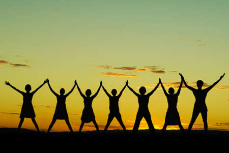 surrender: Happy celebrating women at sunset or sunrise standing elated with arms raised up above their heads Stock Photo
