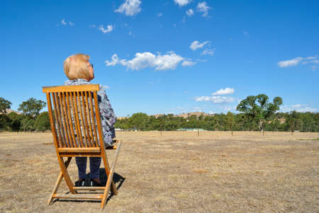 adult 80s: Woman relaxing on deck chair in Australian countryside Stock Photo