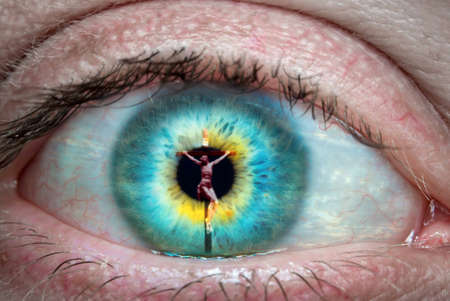 Close up of eye with Jesus Christ on the cross reflected in it
