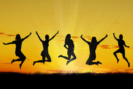 Group of friends jumping with joy at sunrise silhouetted