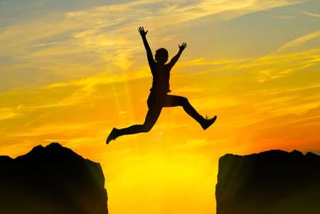 Siluetta del giovane che salta sopra le montagne al tramonto Archivio Fotografico
