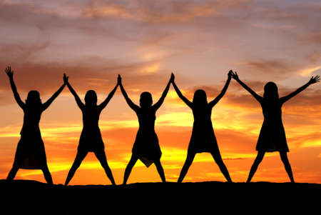 elated: Happy celebrating women at sunset or sunrise standing elated with arms raised up above their heads Stock Photo