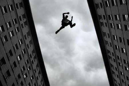 saltando: Hombre que salta sobre la azotea del edificio contra el cielo gris de fondo