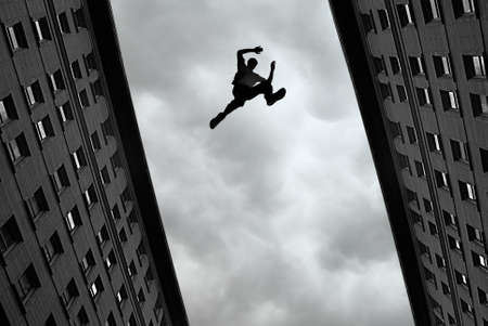 high view: Man jumping over building roof against gray sky background