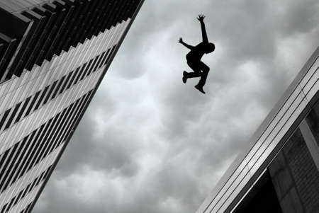 Man jumping over building roof against gray sky background