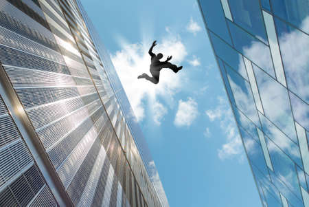 leap: Man jumping over building roof against blue sky background Stock Photo