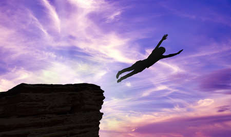 man jump: Silhouette of a man jumping off a cliff over purple background Stock Photo