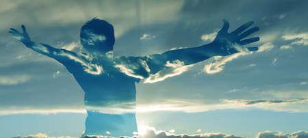 両手を大きく開いて男のシルエットの二重露光イメージ