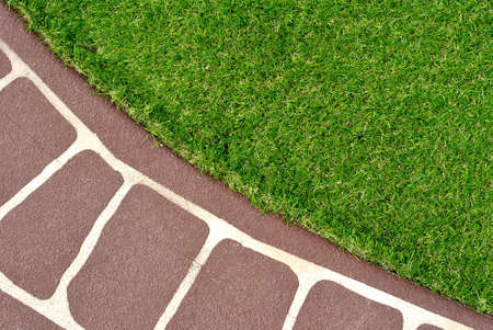 Combinations of stenciled concrete floor and green artificial grass Archivio Fotografico