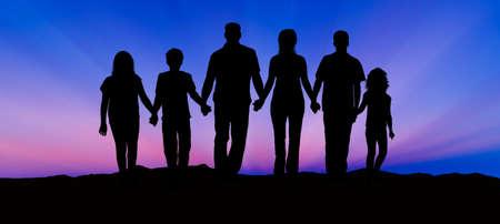 siluetas de mujeres: Silueta de una familia que comprende un padre, la madre y los niños caminando en el atardecer