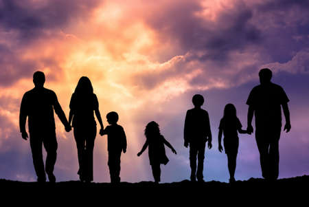 familias unidas: Silueta de una familia que comprende un padre, la madre y los niños caminando en el atardecer