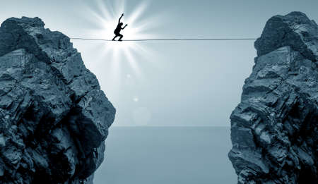 taking a risk: Highline walker in blue sky between two rocks concept of risk taking and challenge