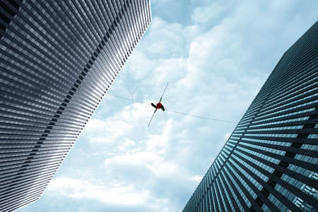 balanza: Highline walker en el cielo azul entre dos edificios concepto de asunción de riesgos y el desafío