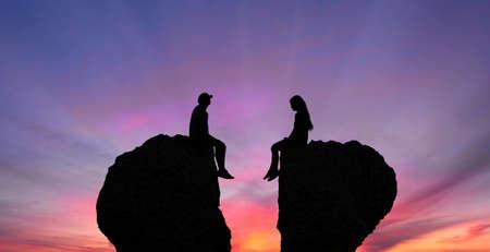 喧嘩失恋として形をした岩の上に座っている若いカップル