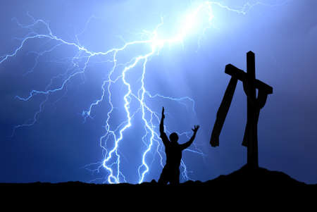 kneeling man: Dramatic sky scenery with a mountain cross and a worshiper
