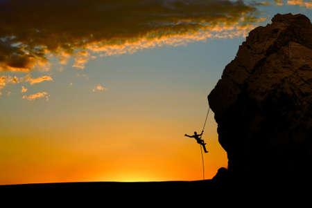 escalando: Silueta de un escalador en una pared vertical sobre puesta del sol amarilla Foto de archivo