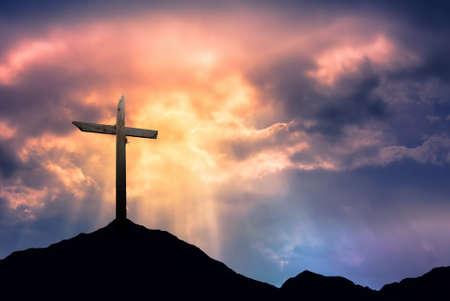 cruz religiosa: Silueta de la cruz al amanecer o al atardecer con los rayos de luz