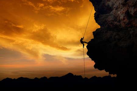 stijger: Silhouet van een klimmer over gele zonsondergang