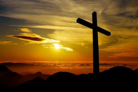 dramatic: Cross silhouette over a dramatic sky at sunset Stock Photo