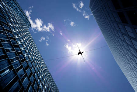 danger: Highline walker en el cielo azul entre dos edificios concepto de asunción de riesgos y el desafío