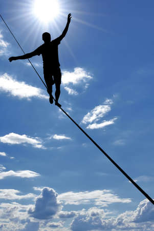 taking a risk: Silhouette of a man on the rope risk taking and challenge concept Stock Photo