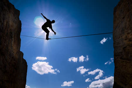 risk taking: Silhouette of man on the rope concept of risk taking and challenge