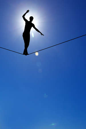 taking a risk: Man balancing on the rope concept of risk taking vertical image