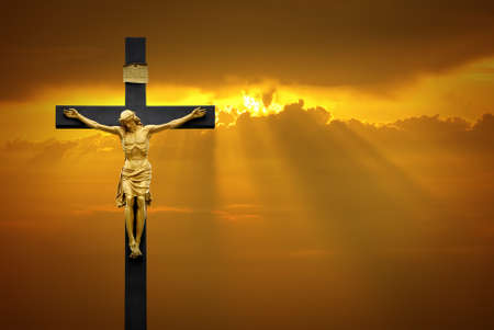 Jesus Christ on the cross over sky background with a shining celestial light from above