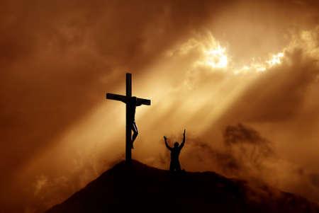 pardon: Silhouette d'un homme priant devant une croix au coucher du soleil concept de religion