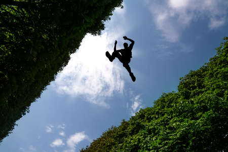 stunt: Man jumping over bushes against blue sky background Stock Photo
