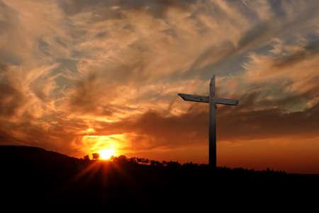 Silueta de la cruz cristiana al amanecer o al atardecer con los rayos de luz