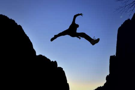 brincando: Hombre que salta sobre precipicio entre dos montañas