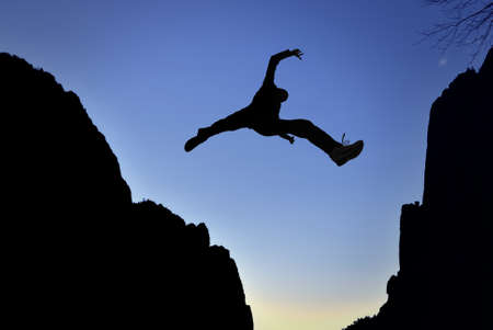 Man jumping over precipice between two mountains