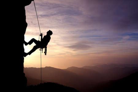 Silhouet van een klimmer op een verticale wand dan prachtige zonsondergang Stockfoto