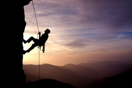 Silhouette of a climber on a vertical wall over beautiful sunset 免版税图像 - 52248599