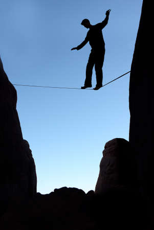 taking a risk: Silhouette of man on the rope concept of risk taking vertical image Stock Photo