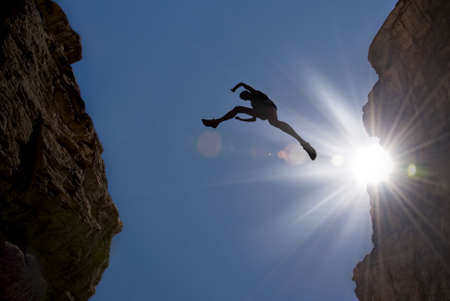 Muž skákání přes propasti mezi dvěma horami