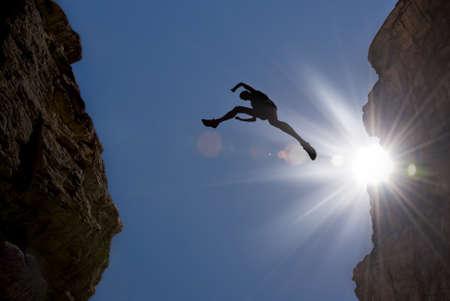 Uomo che salta sopra precipizio tra due montagne Archivio Fotografico - 52677743