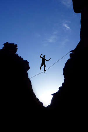 risk taking: Silhouette of man balancing on the rope concept of risk taking and challenging Stock Photo