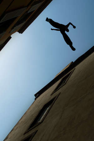 taking a risk: Man jumping from roof to roof concept of risk taking and challenge Stock Photo