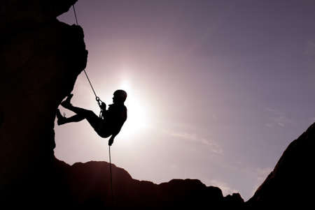 mountain sunset: Silhouette of a climber on a vertical wall over beautiful sunset