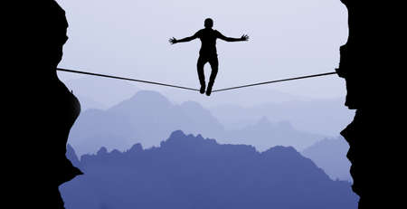 risk taking: Silhouette of man balancing on the rope concept of risk taking Stock Photo