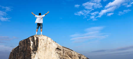 spirituality: Winner man standing on the top of mountain concept of success