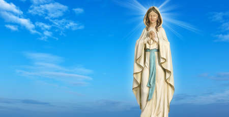 blessed virgin mary: Statue of the Virgin Mary over blue sky background Stock Photo