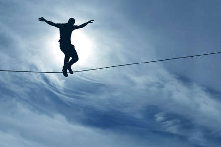 Silhouette of man balancing on the rope concept of risk taking Imagens