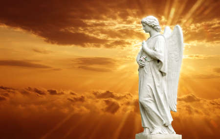christian women: Beautiful angel over yellow magical sky with rays of light