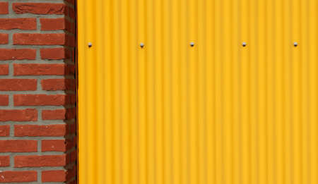 corrugate: Corrugated steel sheet and brick wall background Stock Photo
