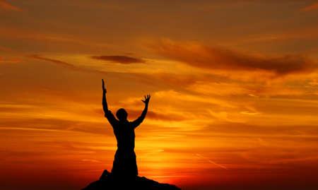 宗教の日没の概念で祈っている人のシルエット