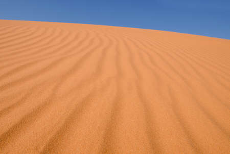 inhospitable: Detail of ripples in orange sand dune on a clear day Stock Photo