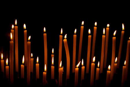 liturgy: Burning candles against black background